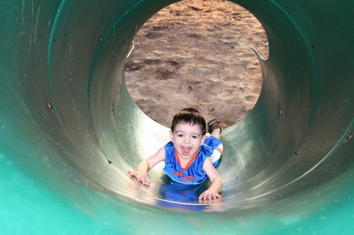 Boy Laughing And Playing With The Slide